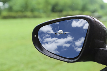 Reflection of airplane in car mirror
