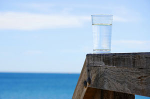 glass of water with ocean in background